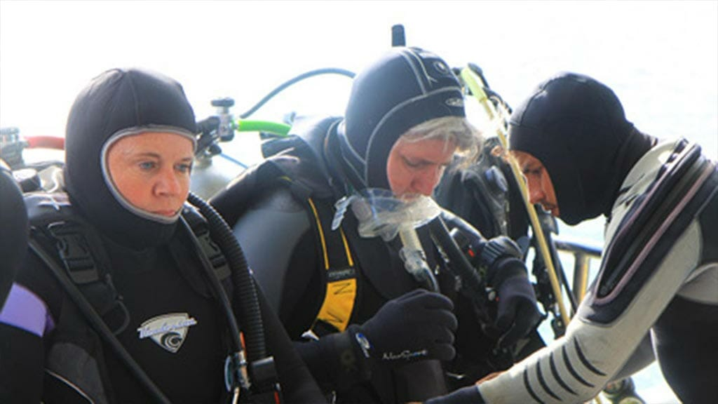 tourists prepare their dive equipment with guide aboard the Humboldt Explorer yacht Galapagos scuba cruise