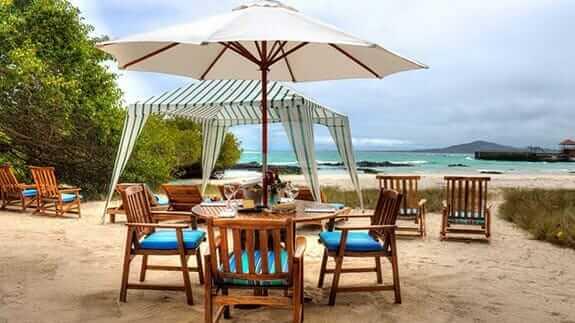 shaded table on the beach at the isabela beach house, puerto villamil, galapagos islands