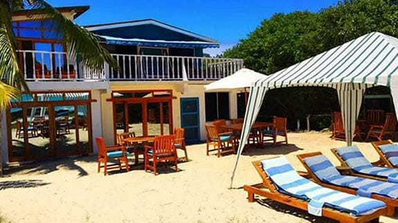 loungers and tables on the beach at the isabela beach house, galapagos islands