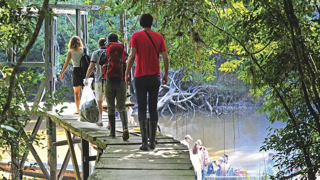 tourists at the wooden dock to board canoe at Jamu lodge