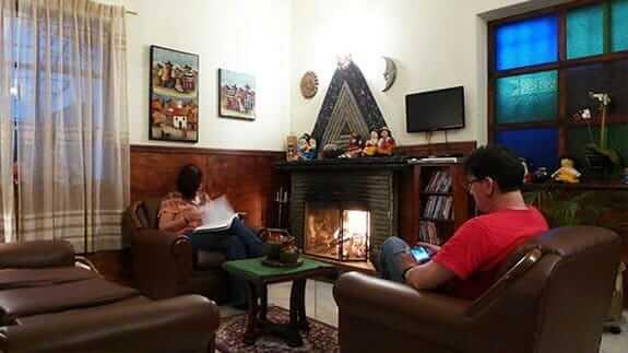 jhomana hostal quito ecuador - two tourists relax next to an open fire