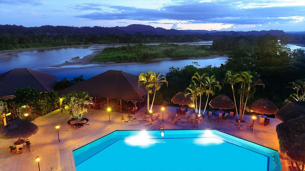 aerial view of Casa del suizo tena lodge and swimming pool with rainforest and river backdrop