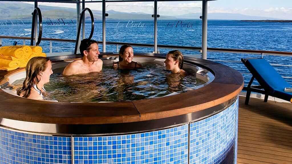 La Pinta Galapagos cruise ship - tourists enjoy the open air hot tub with great ocean views