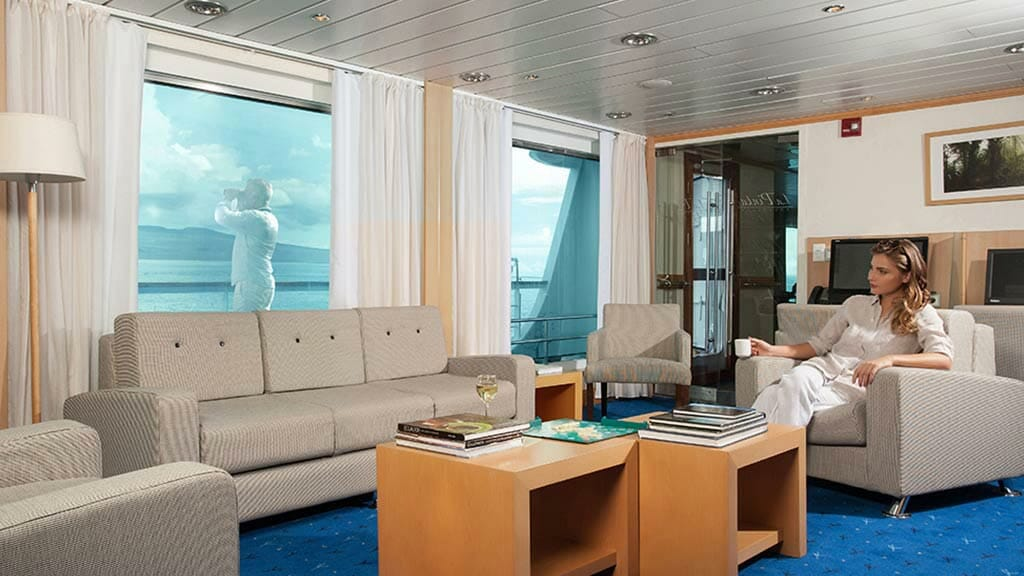 La Pinta cruise ship - tourist enjoys a coffee in the lounge at Galapagos islands