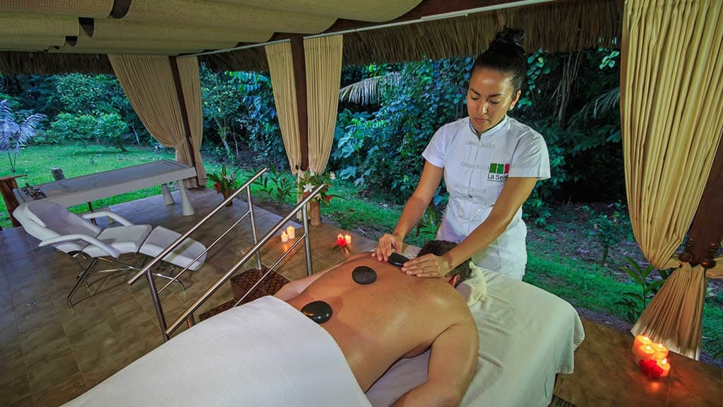guest enjoying a hot stone massage at the La Selva lodge jungle spa
