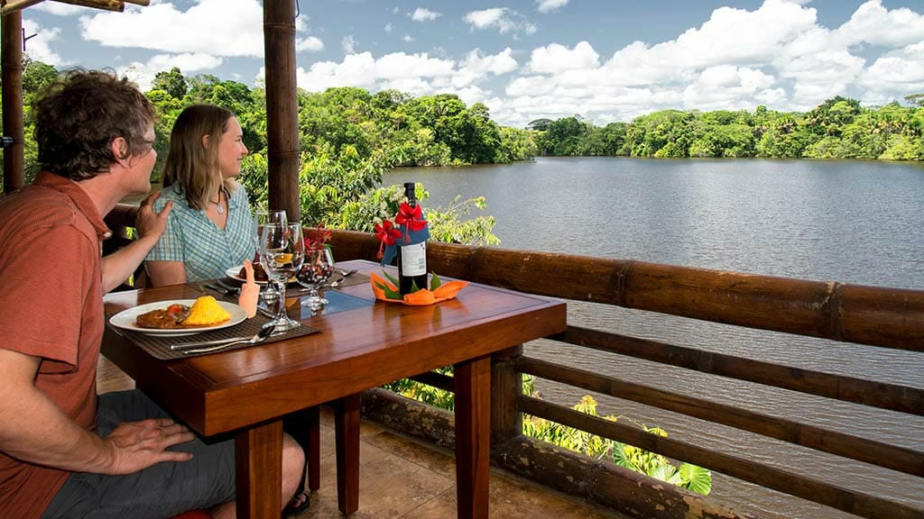 guests enjoy lunch view lake and jungle views at La Selva lodge