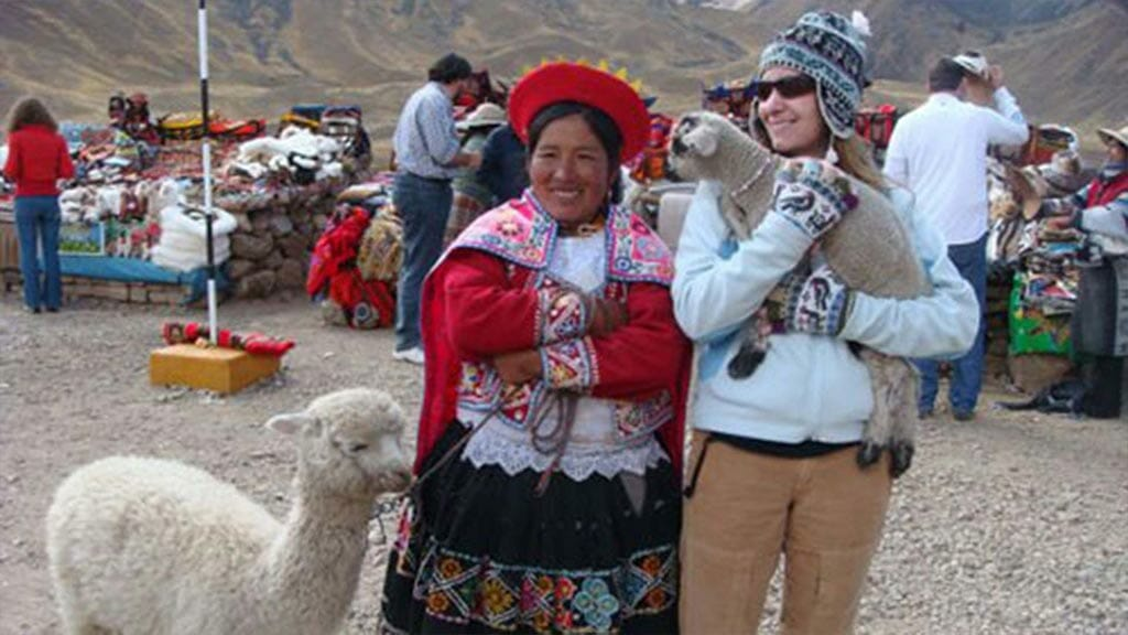 tourists carrying a lamb with lady in peru