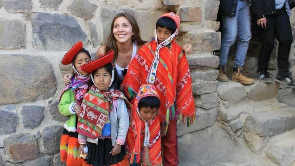 tourist posing with peru children in red ponchos cusco peru