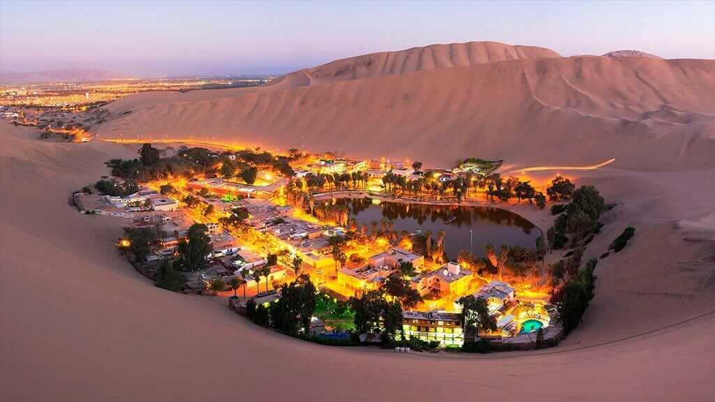 huacachina oasis illuminated at night with sand dunes in peru