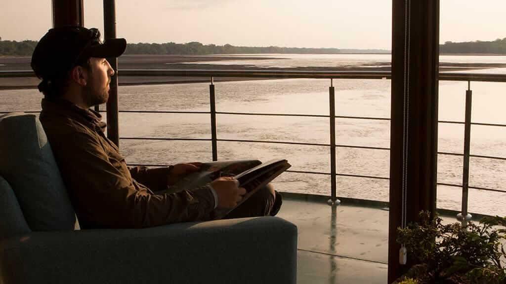 Manatee amazon explorer ecuador - tourist reads a book on his private balcony with jungle views