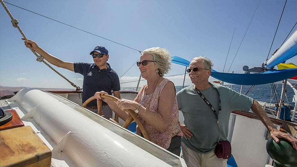 Galapagos tourists take the wheel of the mary anne yacht