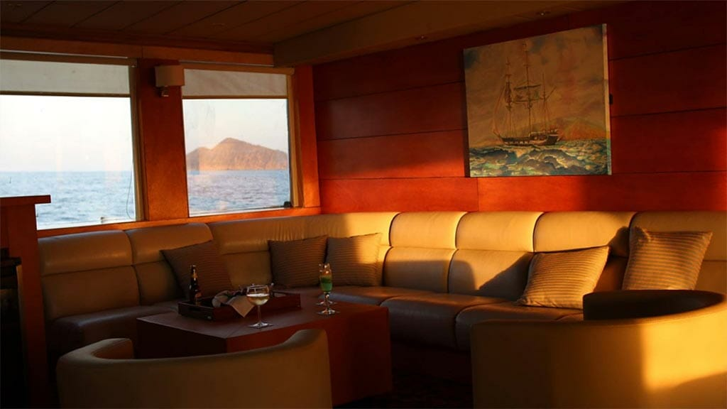 comfortable lounge area with leather sofa aboard the Millenium Galapagos yacht