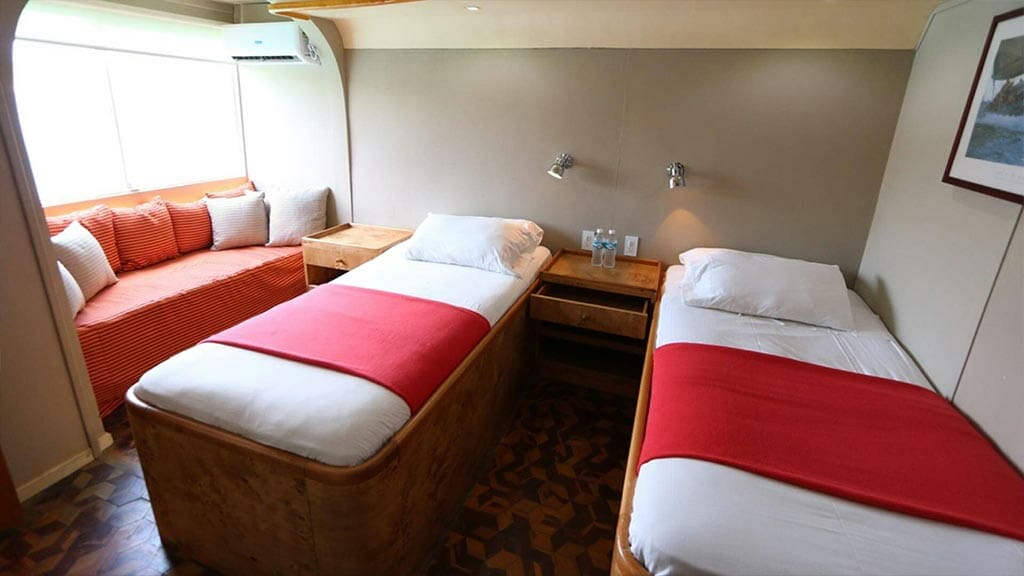 twin bed cabin with sofa aboard the Millenium Galapagos yacht
