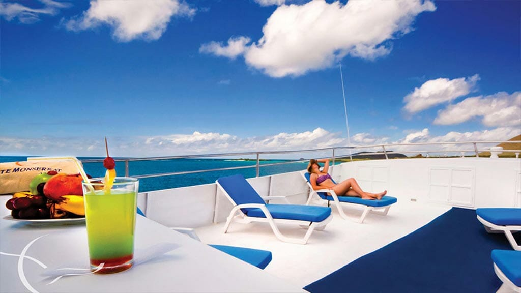 a tourist relaxes on the Monserrat yacht sun deck while colorful cocktails are served