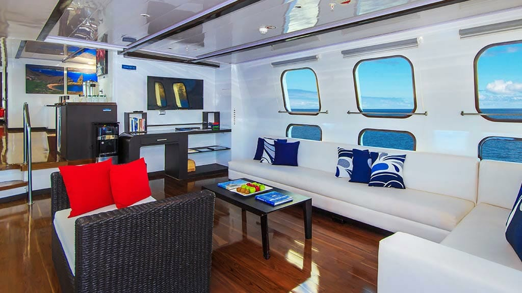 comfortable lounge social area with sofa and wooden floor aboard the Natural Paradise yacht at Galapagos