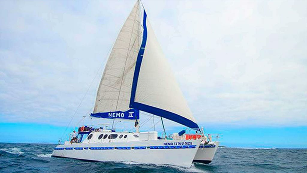 nemo 2 catamaran yacht with sails up at the galapagos islands