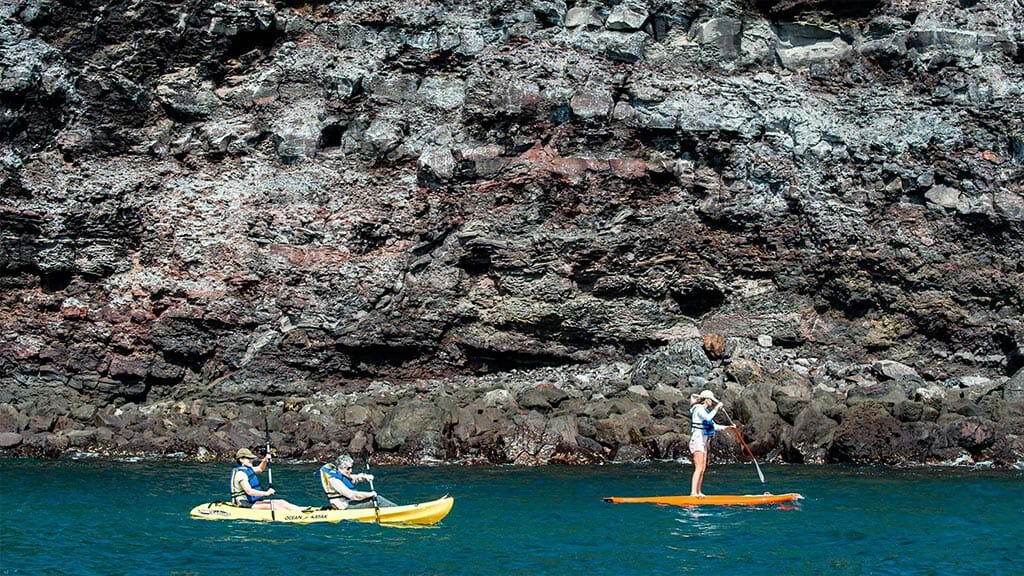 Origin yacht - tourists enjoy kayaking and paddle boarding at galapagos