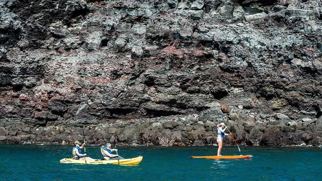 Origin yacht - tourists enjoy kayaking and paddle boarding at galapagos