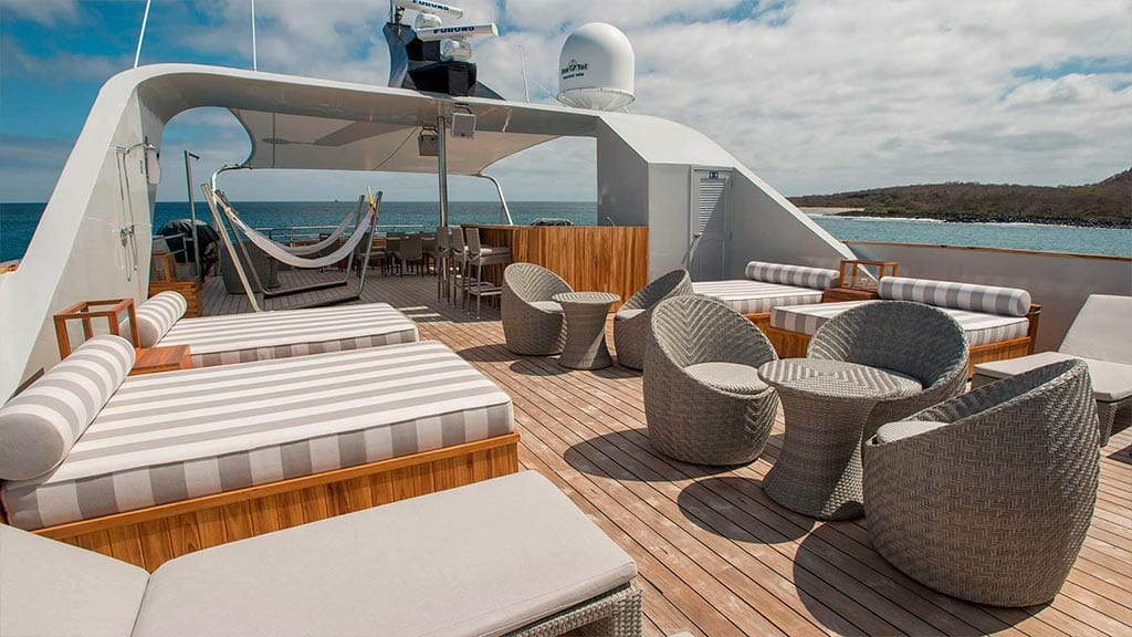 Origin yacht Galapagos cruise - spacious wooden decked sun deck with loungers and ocean views