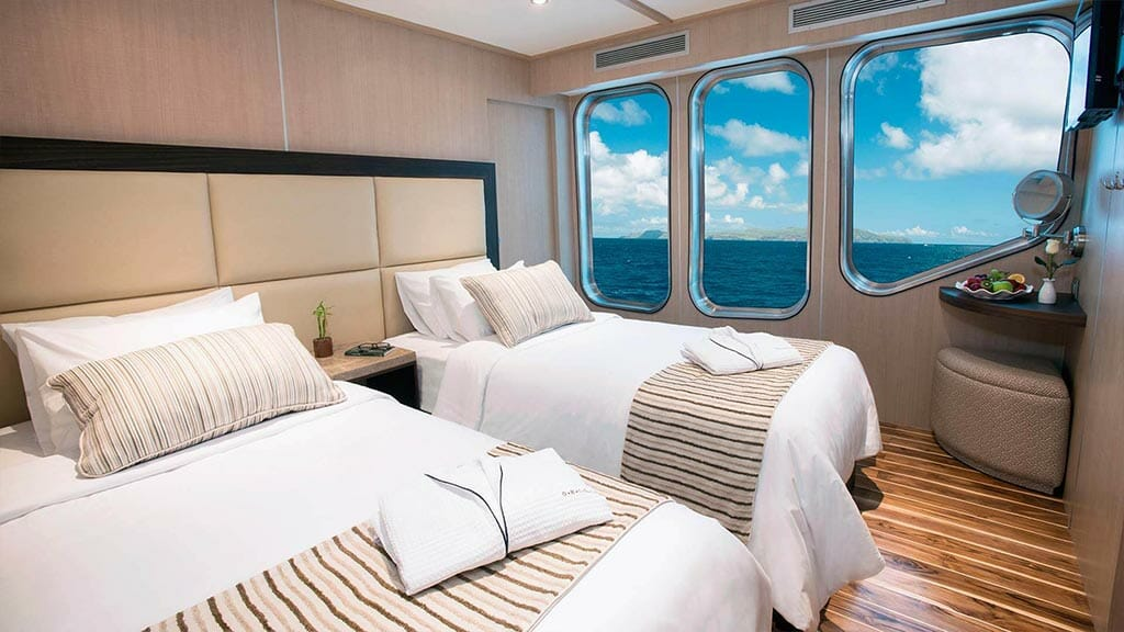 twin bed cabin with wooden flooring and large windows aboard the Origin Galapagos cruise yacht