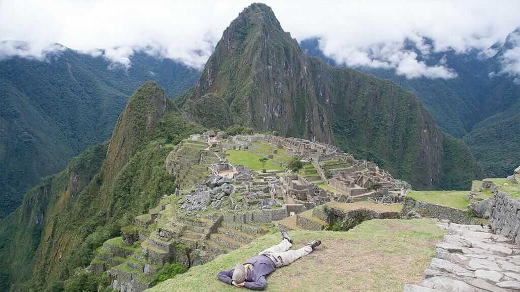 tourist lying on his back at machu picchu ruins peru