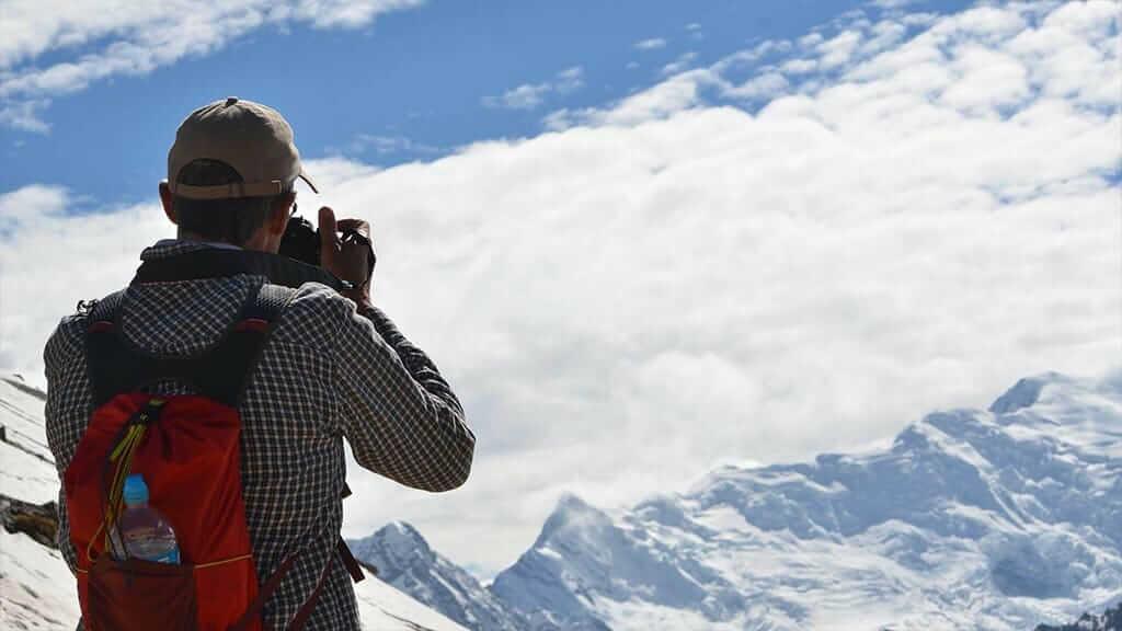 tourist takes a photo of glacial snow capped mountain on the Salkantay trek Tour