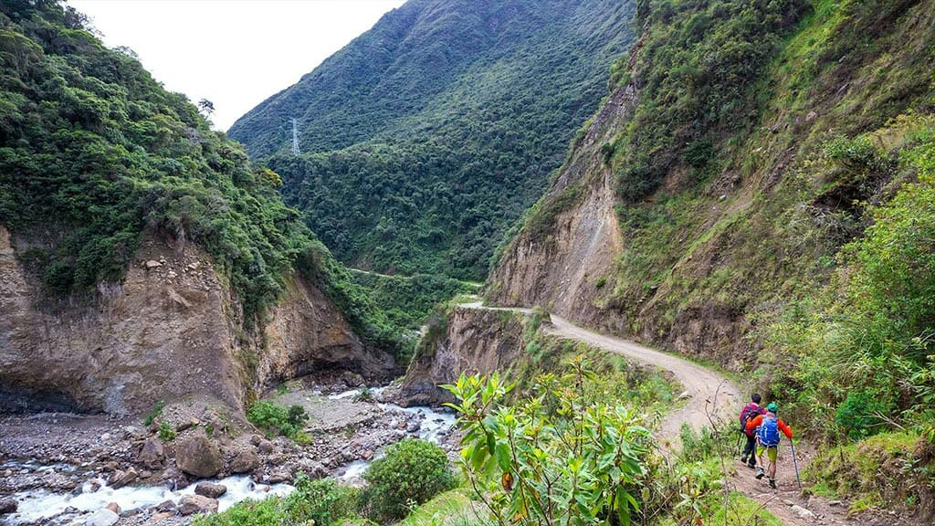 tourists hike in a river valley on the Salkantay trek route
