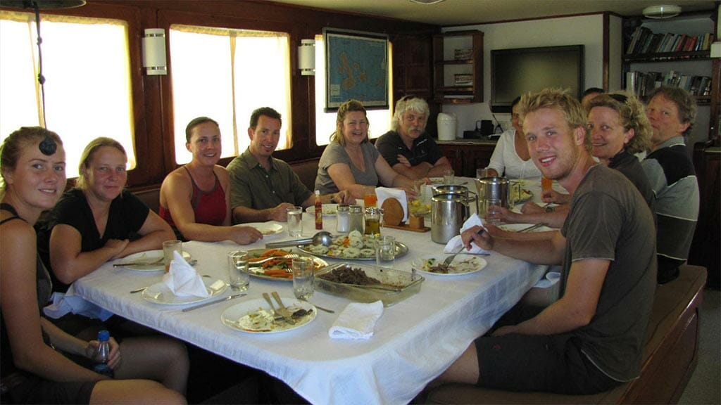 tourists enjoy a communal meal together on the samba galapagos cruise