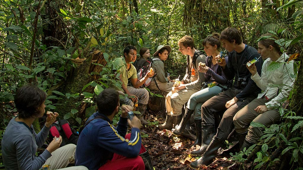 tourists take a break with their guide during a rainforest trek at Sani lodge ecuador