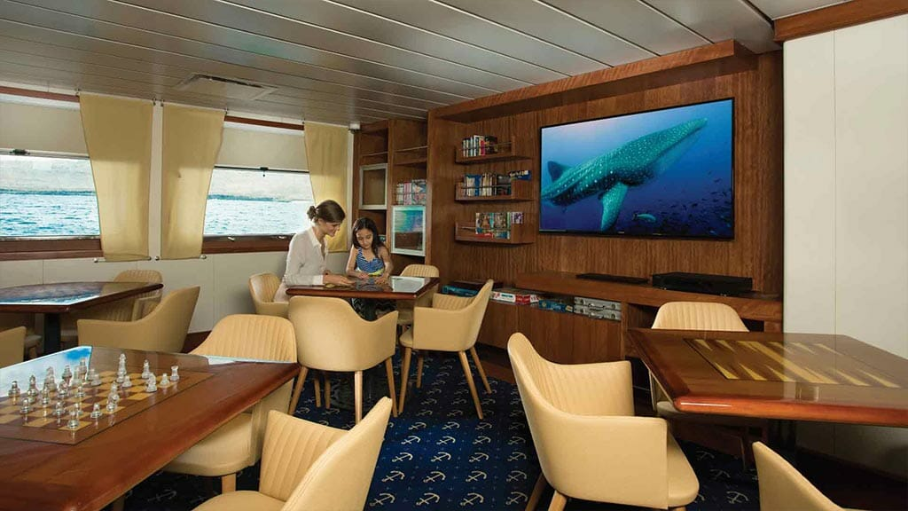 santa cruz ii galapagos cruise ship - games area with chess, tv videos and library books