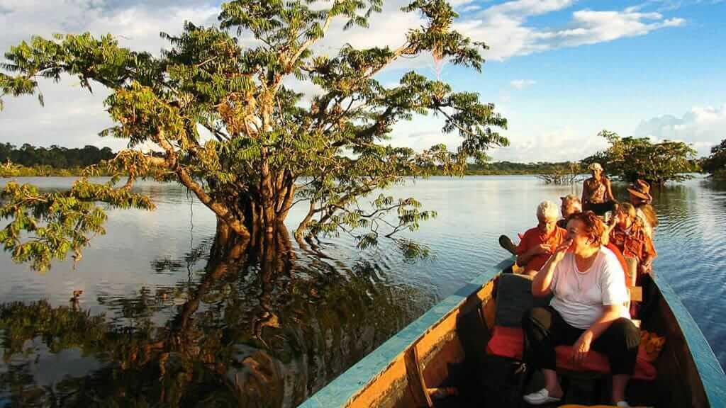 tourists canoe on Cuyabeno Lake on a Tapir Lodge tour