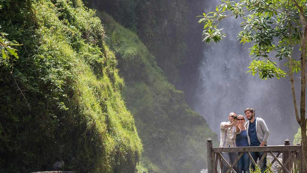 three-tourists-in-a-waterfall