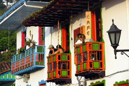 tourists drinking coffee on colorful balconies of the colombia coffee triangle