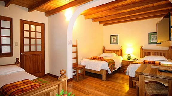 triple room with wooden floors at hotel vieja cuba quito