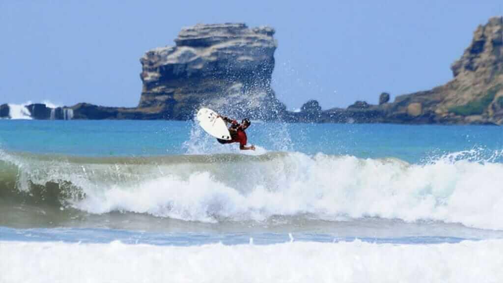 a surfer jumping from the waves at ayampe beach ecuador