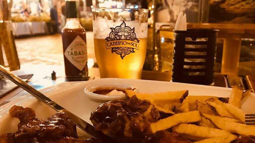 camino del sol beer and chicken wings at a pub in ecuador