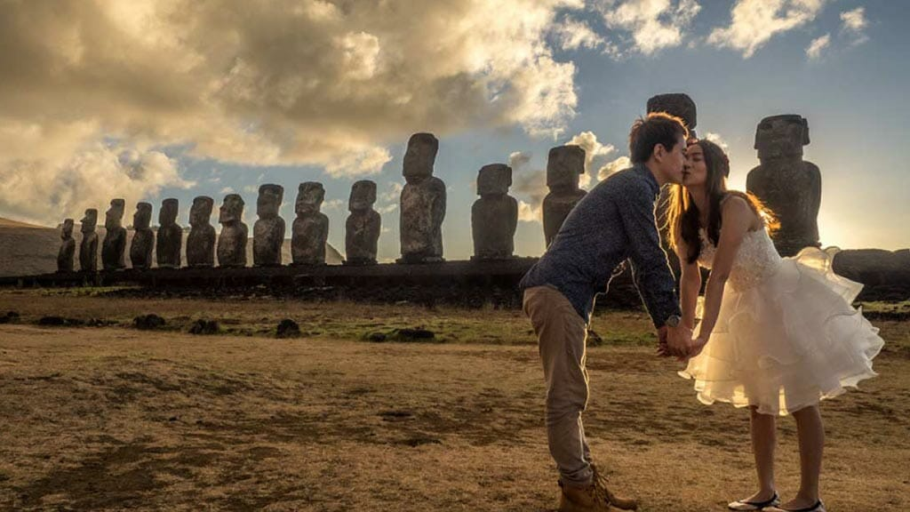 easter island honeymoon - a couple kiss in front of the rapa nui moai statues