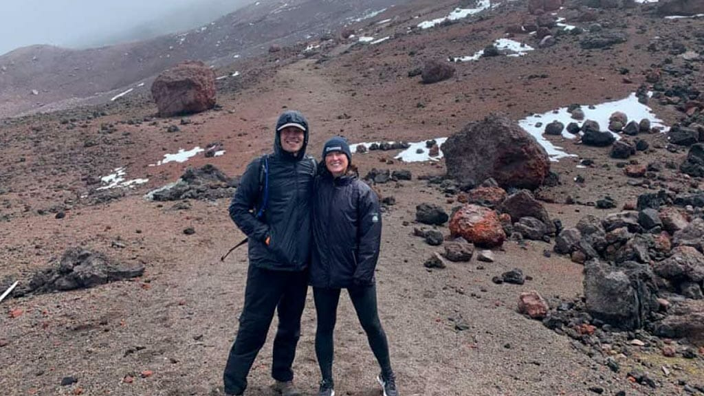 honeymoon couple pose at cotopaxi volcano on their active south america honeymoon vacation
