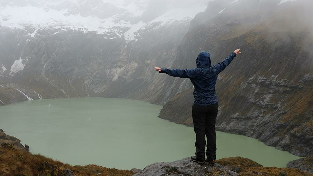 a happy trekker stretches out her arms in the rain at el altar volcano in ecuador