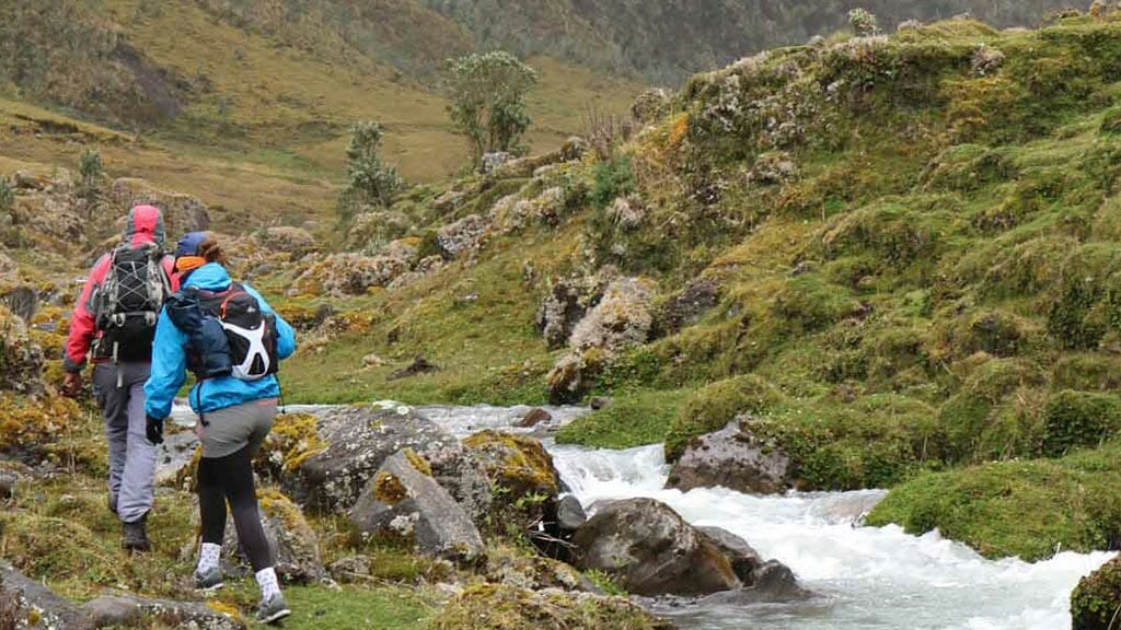 two tourists on the el altar trek in ecuador walking besides a stream