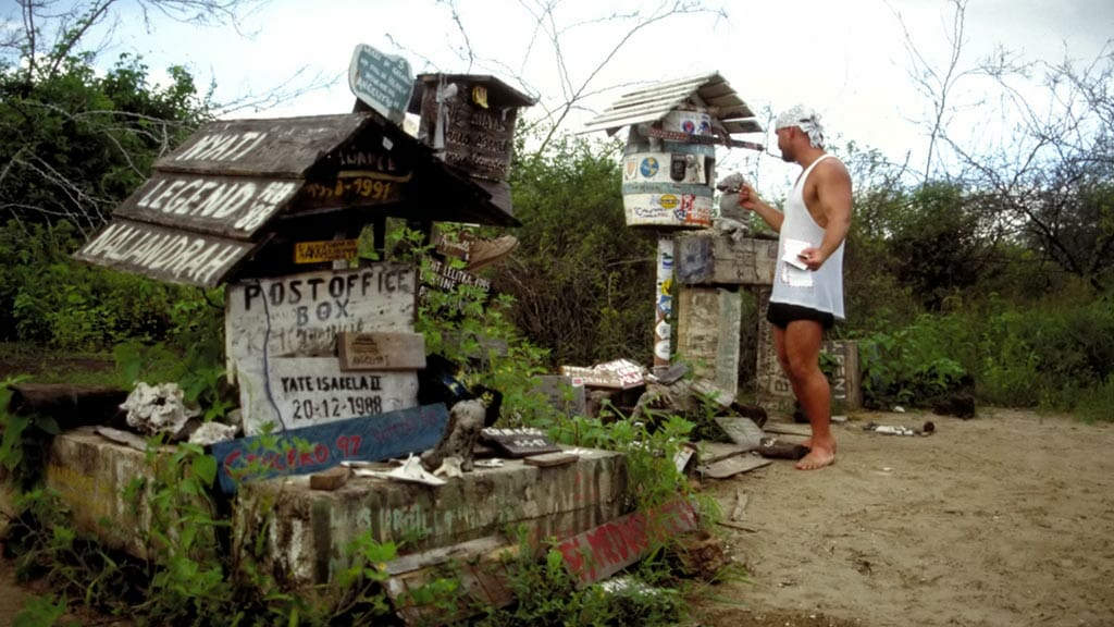 a tourist leaves his post card at post office bay on floreana island galapagos