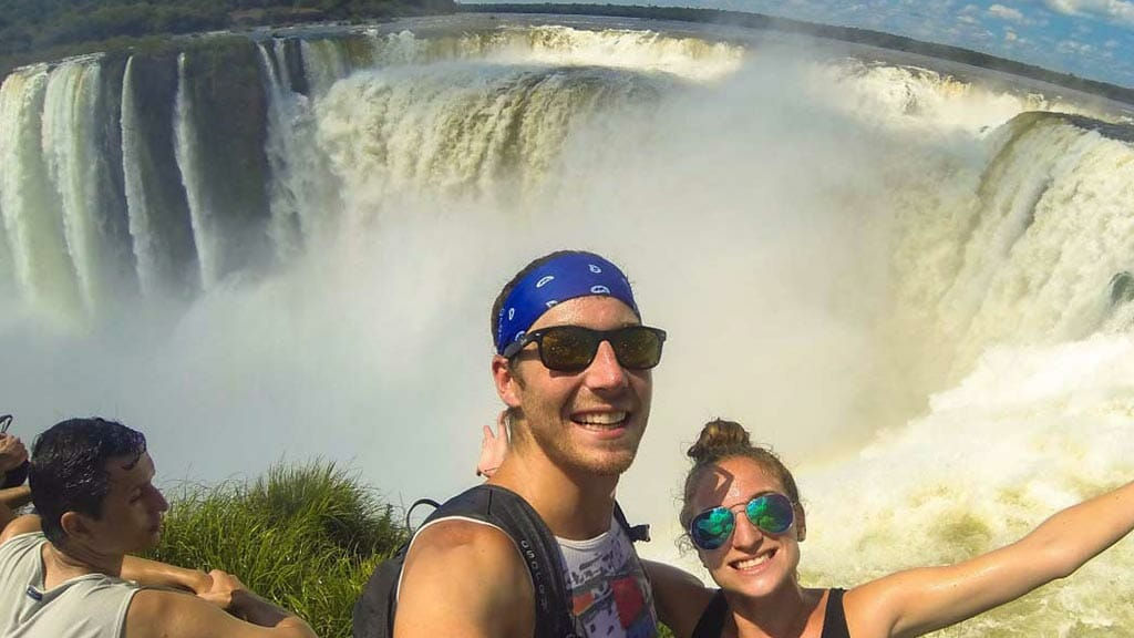 iguazu national park honeymoon couple posing with huge waterfall