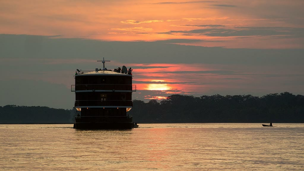 manatee amazon river cruise ship sailing at sunset