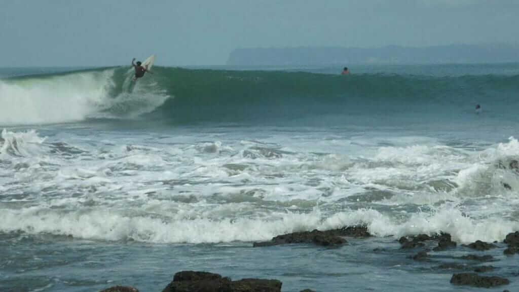 a surfer catches a wave break at mompiche beach on ecuador's ruta del sol