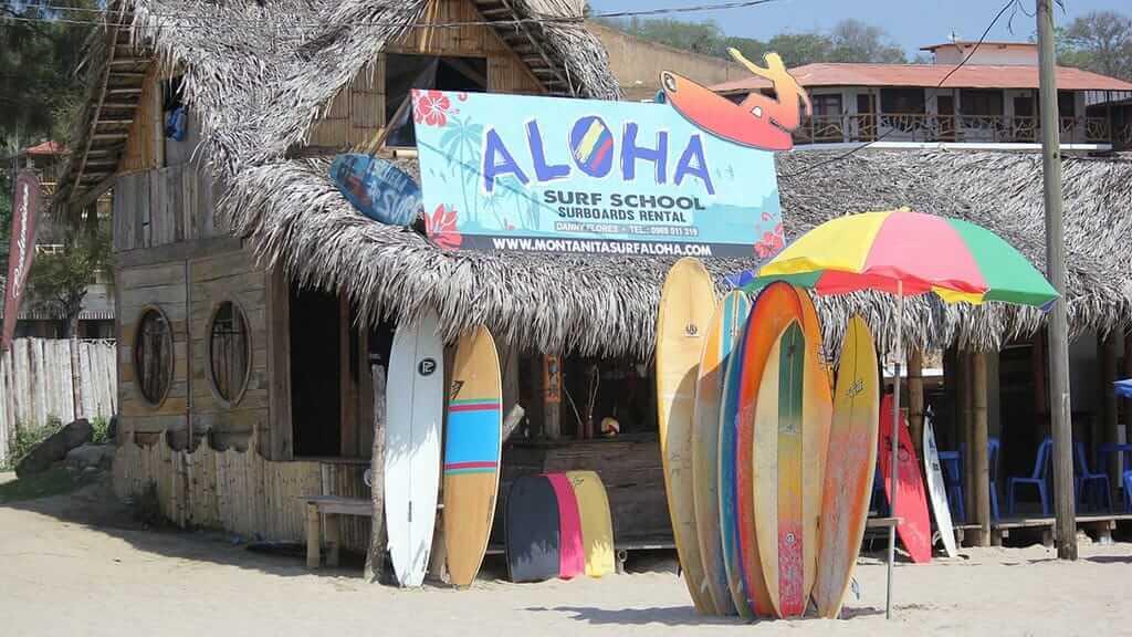 surf boards outside thatched hut at montañita ecuador beach