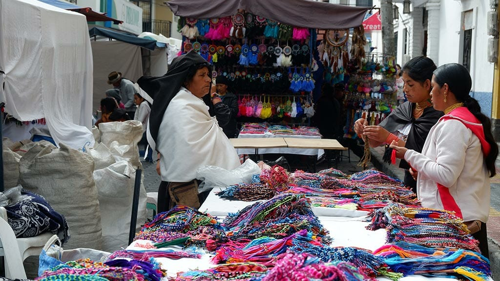 indian woman selling colorful wrist bands at otavalo market ecuador