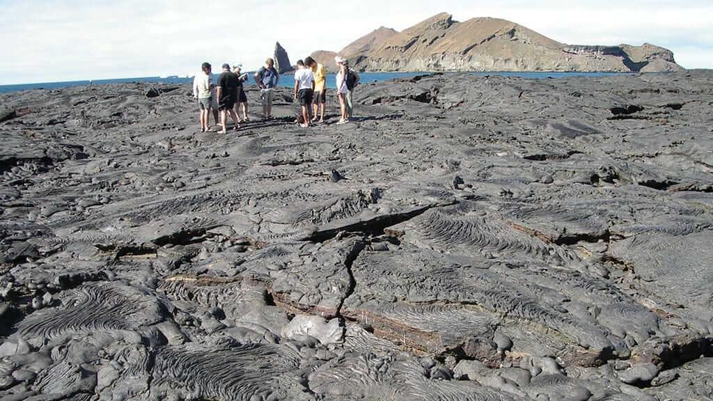 tourists trek on a huge black lava field at sullivan bay on santiago island galapagos