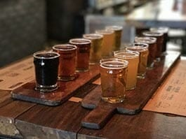 different types of ecuador beer lined up on a wooden platter