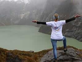 a trekker reaches el altar ecuador volcano peak to view the lake