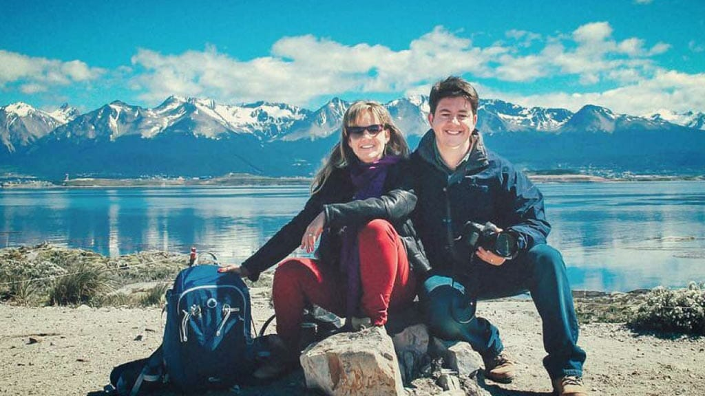 married couple pose in front of ushuaia mountains in argentina